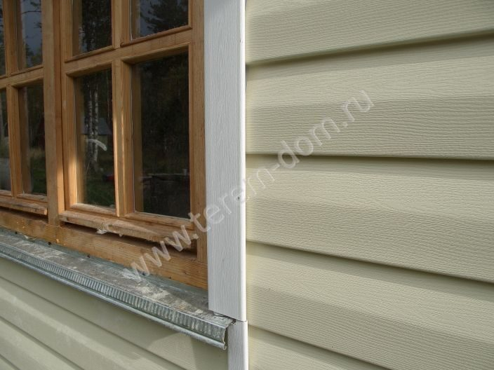 Закрыть окно. обшивка сайдингом окна дома.  Видны элементы примыкания сайдинга к раме и подоконнику-отливу.  Терем-Дом.